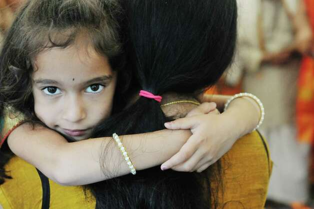 Sinchana Keshavan, 5, of Latham, is held by her mother, Pooja Keshavan during a fire ceremony during a celebration of the 39th anniversary of the Hindu Temple Society, on Sunday, June 21, 2015, in Loudonville, N.Y. During the fire ceremony participants throw offerings into the fire to symbolize that nothing belongs to them, everything belongs to the gods, and they are giving back to the gods and asking to be blessed. During the ceremony participants chanted to purify themselves and the universe.    (Paul Buckowski / Times Union) Photo: PAUL BUCKOWSKI / 00032234A