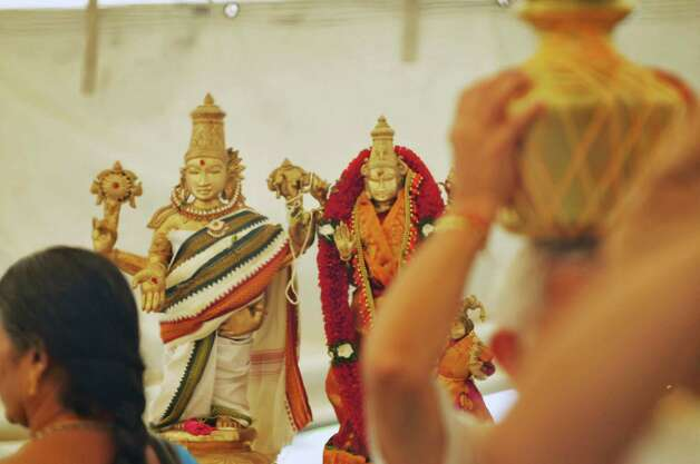 A view of the statues of the gods, Lakshmi and Narayana are seen during a fire ceremony during a celebration of the 39th anniversary of the Hindu Temple Society, on Sunday, June 21, 2015, in Loudonville, N.Y. The two gods are the main deities inside the Hindu Temple in Loudonville. During the fire ceremony participants throw offerings into the fire to symbolize that nothing belongs to them, everything belongs to the gods, and they are giving back to the gods and asking to be blessed. During the ceremony participants chanted to purify themselves and the universe.    (Paul Buckowski / Times Union) Photo: PAUL BUCKOWSKI / 00032234A