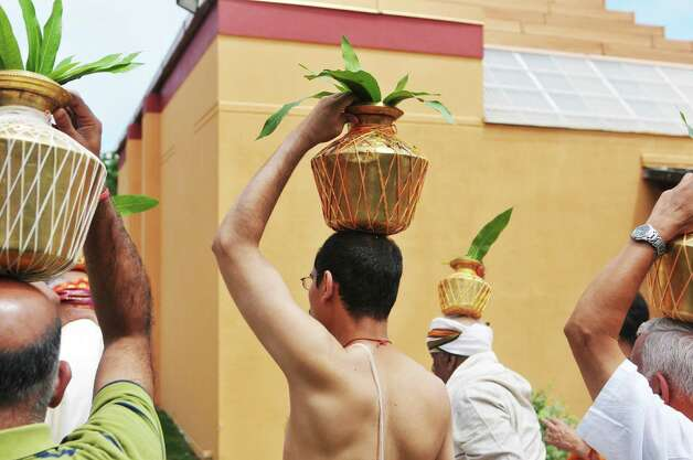 Members of the Hindu Temple Society process around the outside of the Hindu Temple during a celebration of the 39th anniversary of the Hindu Temple Society, on Sunday, June 21, 2015, in Loudonville, N.Y. Some participants hold metal pots filled with water on their heads. The water was later poured on the deities inside the temple to transfer energy to the gods.    (Paul Buckowski / Times Union) Photo: PAUL BUCKOWSKI / 00032234A