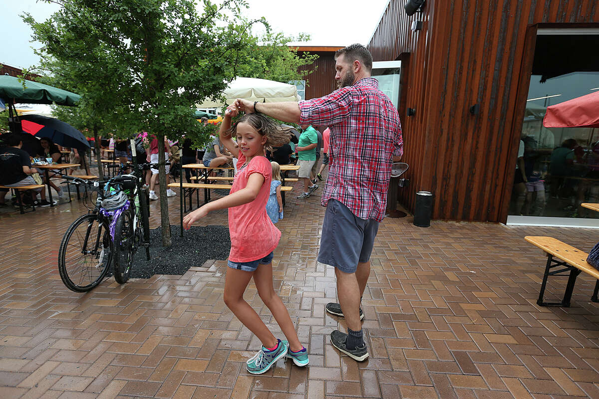 Ken Carter, 41, dances with daughter Thea, 8, in the rain during the first FatherFest at the Alamo Beer Co.'s downtown-area brewery. The festival included craft beer and a sausage cook-off.