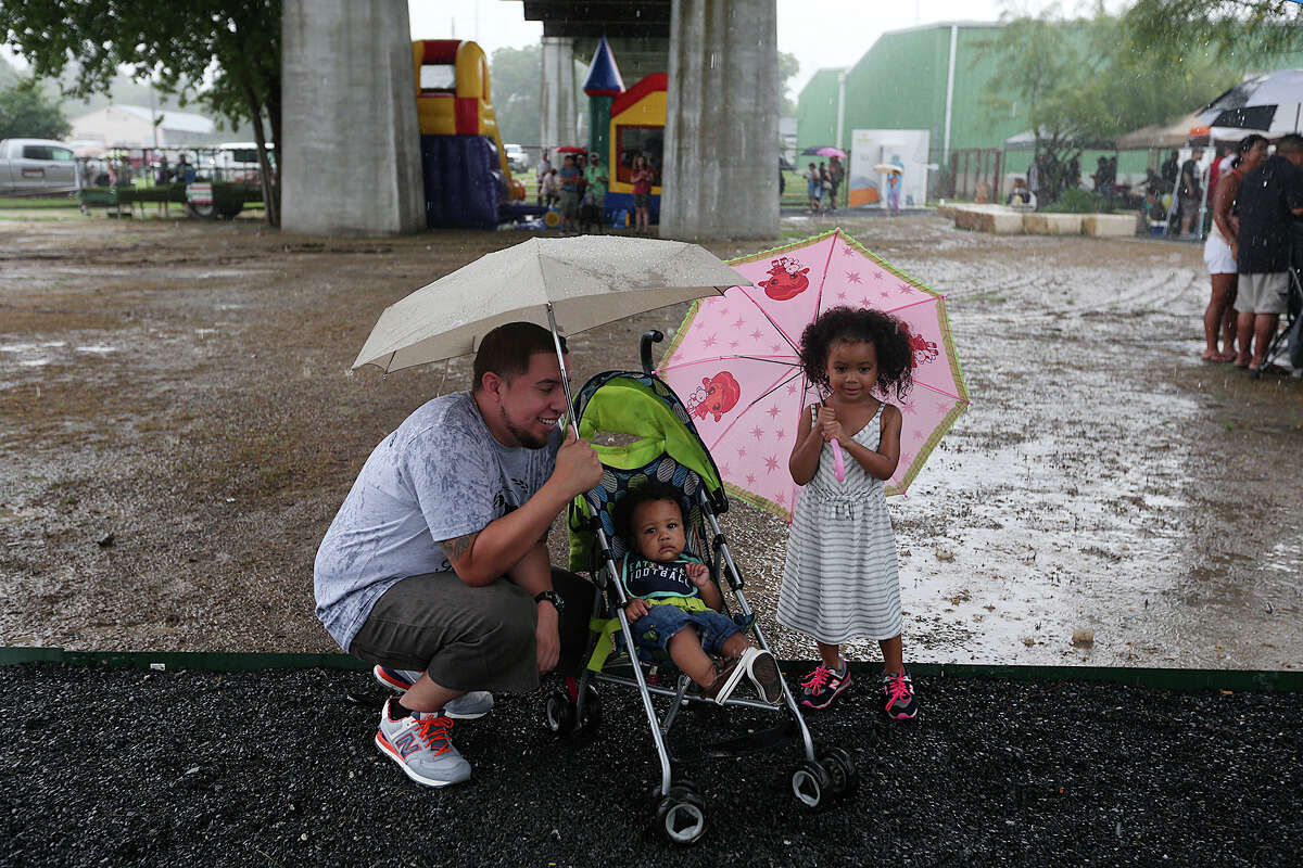 Gerardo Estrada and his children Nasir, 9 months, and Tiana, 3, seek shelter from the rain under the Hays Street Bridge. The festival also included food trucks and live music.