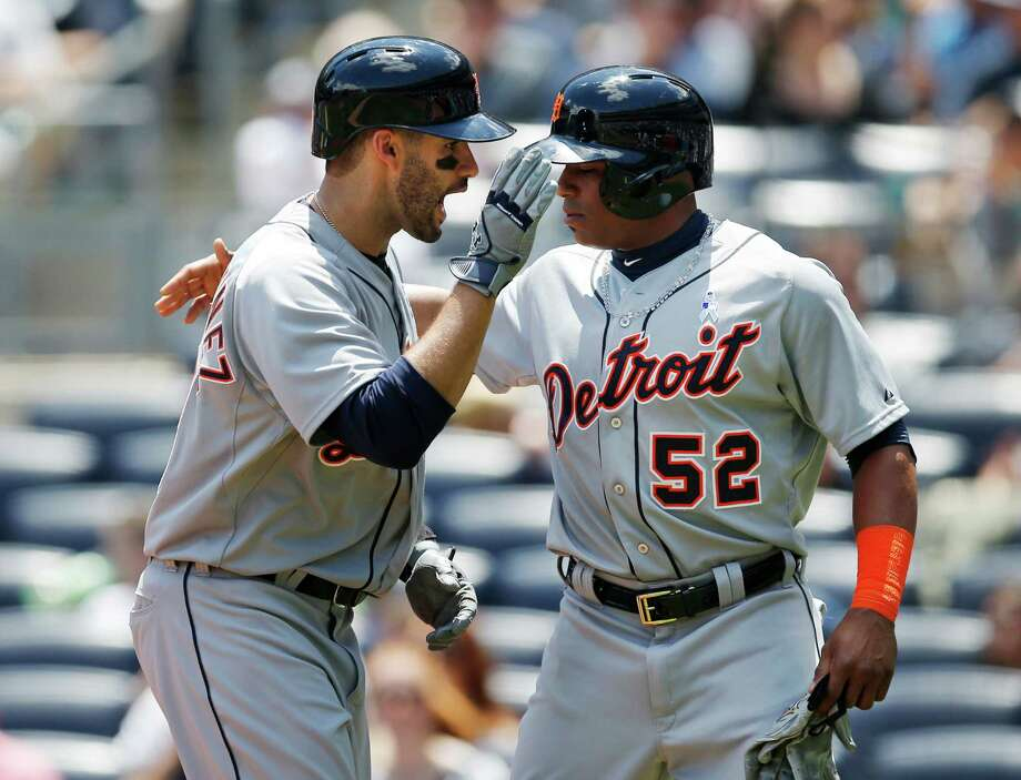 Detroit Tigers J.D. Martinez, left, celebrates with the Tigers Yoenis Cespedes (52) after hitting a first-inning, two-run, home run off New York Yankees starting pitcher Masahiro Tanaka in a baseball game at Yankee Stadium in New York, Sunday, June 21, 2015.  (AP Photo/Kathy Willens) ORG XMIT: NYY103 Photo: Kathy Willens / AP
