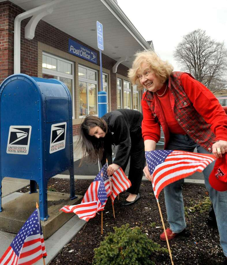 Gabriella Ruggiero, left, and Mae Schmidle, a former state representative for Newtown, festoon the new Hawleyville Post Office with flags during the grand opening in Newtown on Monday, March 15, 2010. Photo: Michael Duffy / The News-Times