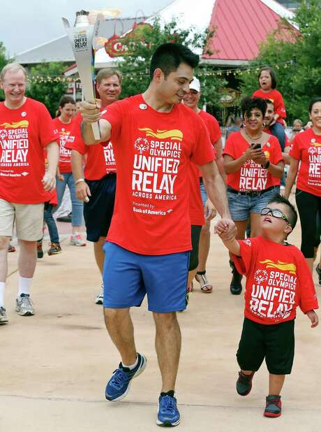 Bank of America employee Jose Alarcon carries the Special Olympics Flame of Hope around Morgan's Wonderland with his son Rodrigo Alarcon, 5, as other torch-bearers follow, Sunday June 21, 2015 part of the Special Olympics Unified Relay Across American. The Special Olympics World Games Los Angeles 2015 will be held July 25-August 2, 2015. For more information on the Special Olympics World Games Los Angeles 2015 visit www.la2015.org. For more information on Morgan's Wonderland visit www.morganswonderland.com. Photo: Edward A. Ornelas, Staff / San Antonio Express-News / © 2015 San Antonio Express-News