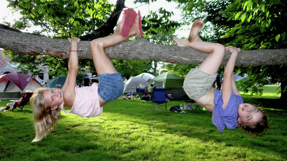 Katherine Scully and Eliza Paura swing from a tree at the annual potluck supper and overnight campout event Friday night on the Great Lawn of the Pequot Library. Photo: Mike Lauterborn / For Hearst Connecticut Media / Fairfield Citizen