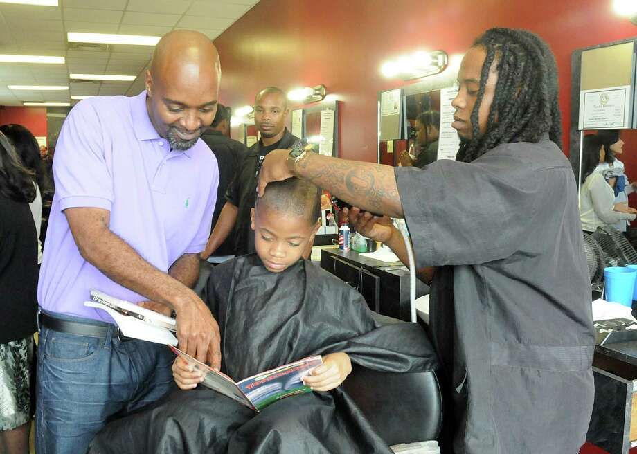 Main Event Barber Shop owner Andre Lewis reads a book to Amarioe Gregory as barber Jordan Wilson cuts Gregory's hair at the Main Event Barber Shop, 1701 FM 1960 West, during the launching of the Spring ISD Slide into Summer reading program reading program with their Books in Barber shops. Spring ISD will provide books and bookcases to be placed in various barber shops in Spring. Photograph by David Hopper. Photo: David Hopper, Freelance / freelance