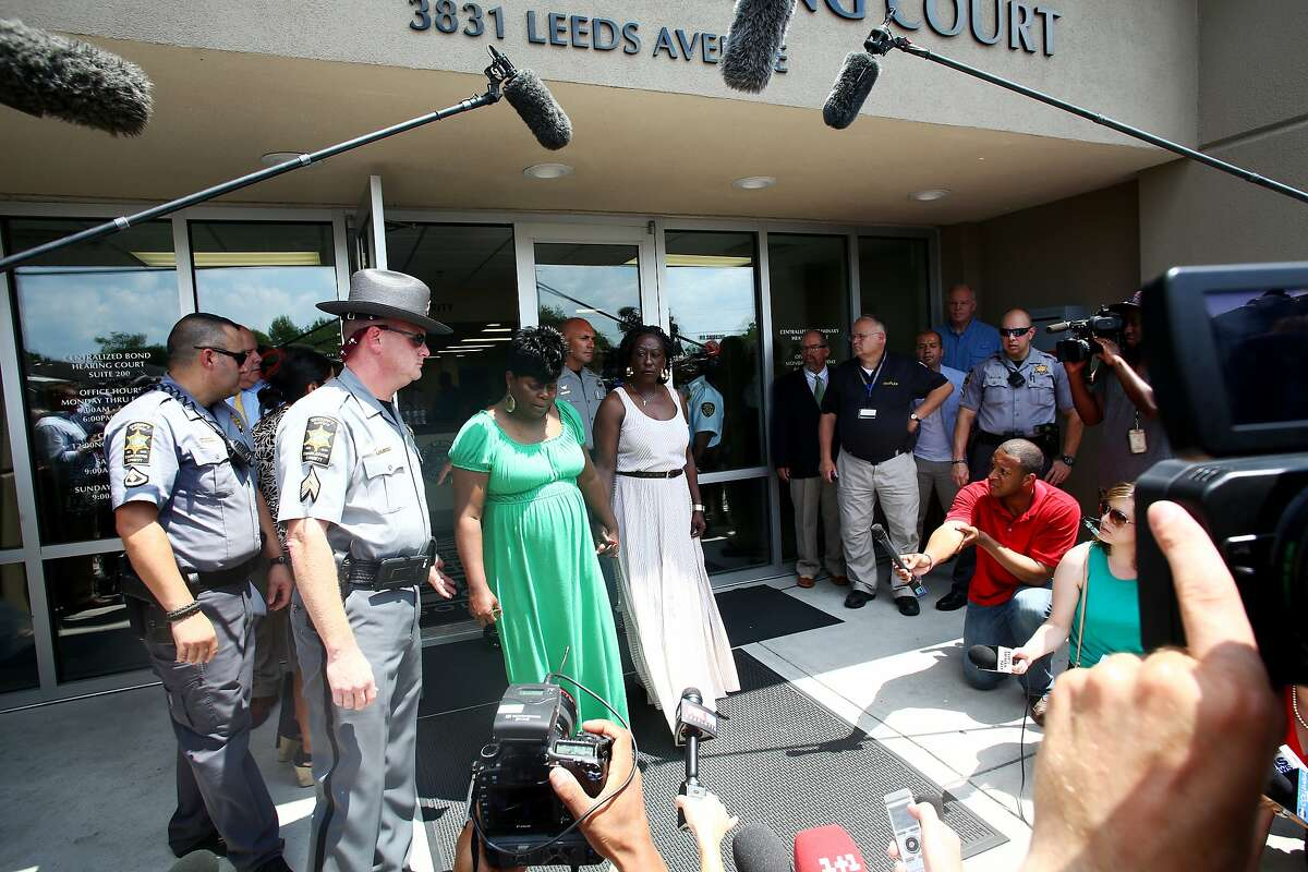 """RETRANSMISSION TO ADD INFO ON COLLIER DURING PROCEEDING -- Nadine Collier, center in green dress, the daughter of Ethel Lance, one of the nine people killed in a church shooting on Wednesday, speaks to reporters outside the courthouse where Dylann Roof, the suspect in the shooting, had his bond hearing Friday, June 19, 2015, in Charleston, S.C. In one of the most poignant moments of the proceeding Collier told Roof, """"You hurt me. You hurt a lot of people. But God forgives you, and I forgive you."""" (Travis Dove/The New York Times)"""