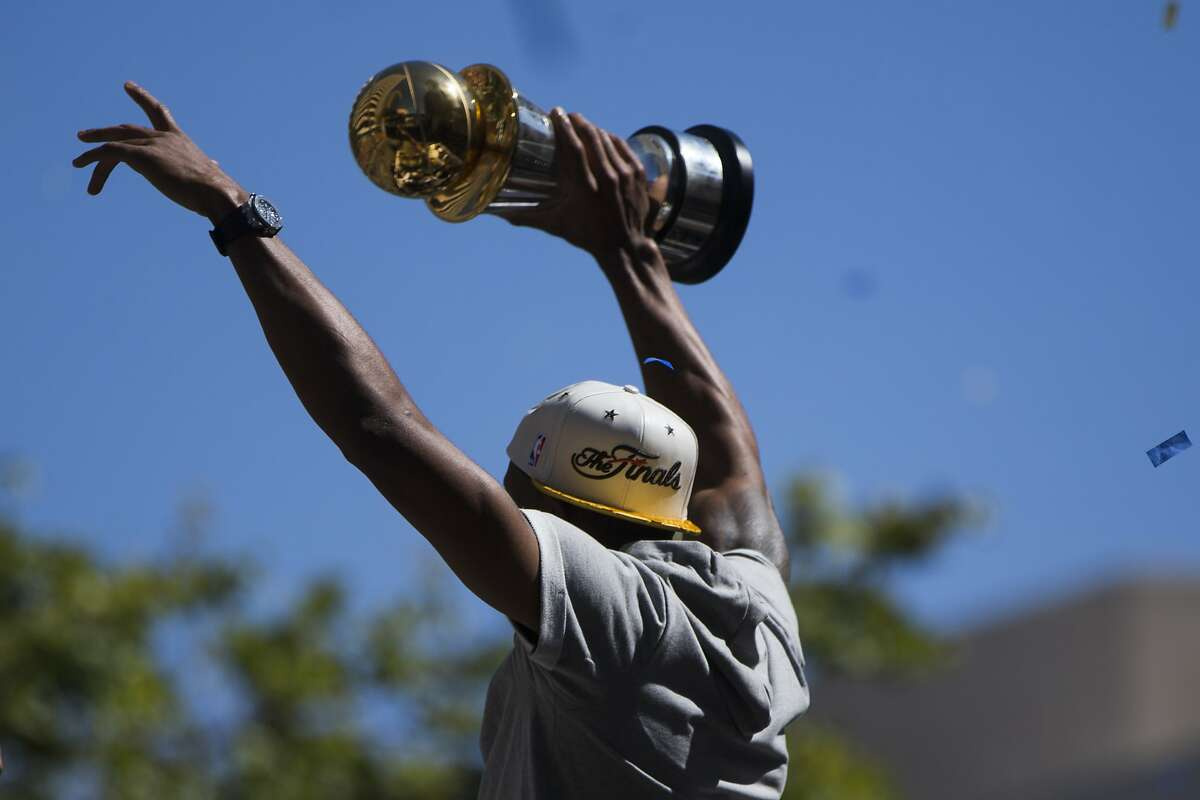OAKLAND, CA - JUNE 19: Andre Iguodala #9 of the Golden State Warriors displays the Bill Russell NBA Finals MVP Trophy during the Golden State Warriors Victory Parade in Oakland, California. Thousands are expected to attend in celebration of the Warriors' first NBA title in 40 years. (Photo by Stephen Lam/Getty Images)