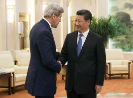 FILE - In this May 17, 2015, file photo, Chinese President Xi Jinping, right, and U.S. Secretary of State John Kerry shake hands prior to a meeting at the Great Hall of the People in Beijing, China. Tensions between the U.S. and China are growing over its island-building in the South China Sea and over suspicions that Beijing was behind a massive hack into a federal government server that resulted in the theft of personnel and security clearance records of 14 million employees and contractors.  (Saul Loeb/Pool Photo via AP, File)