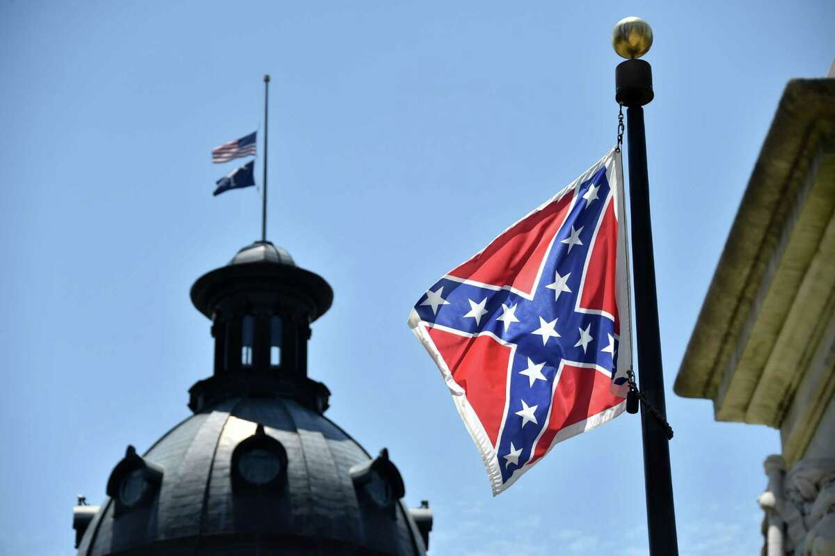 The South Carolina and American flags flying at half-staff behind the Confederate flag erected in front of the State Congress building in Columbia, South Carolina. Gov. Nikki Haley this called for taking down the flag.