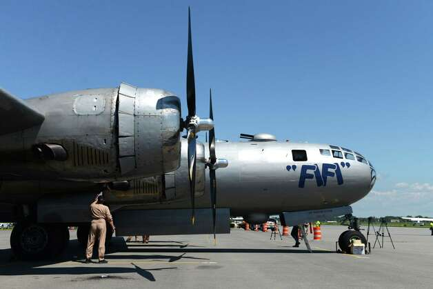 Crew member Steve Colman cleans oil from an engine cover on the Boeing B-29 Superfortress ?Fifi? Monday, June 22, 2015, at Albany International Airport in Colonie, N.Y. The historic WWII bomber is the only flying example of its kind. The plane is viewable to the public between 9 a.m. and 5 p.m. Tuesday at the Million Air terminal at Albany International Airport. (Will Waldron/Times Union) Photo: WW / 00032287A