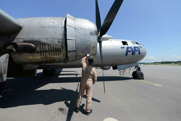 Crew member Steve Colman cleans oil from an engine cowl of Boeing B-29 Superfortress ?Fifi? Monday, June 22, 2015, at Albany International Airport in Colonie, N.Y. The historic WWII bomber is the only flying example of its kind. The plane is viewable to the public between 9 a.m. and 5 p.m. Tuesday at the Million Air terminal at Albany International Airport. (Will Waldron/Times Union) Photo: WW / 00032287A