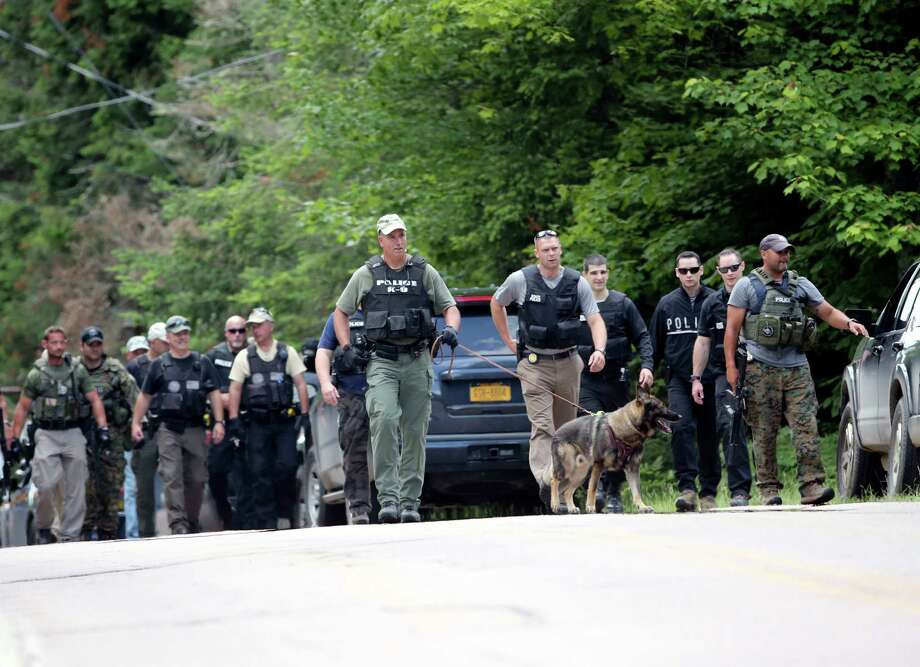 Law enforcement officers walk along a road as the search continues for two escaped prisoners from the Clinton Correctional Facility in Dannemora, on Monday, June 22, 2015, in Owls Head, N.Y. In the more than two weeks since inmates David Sweat and Richard Matt escaped, more than 800 law enforcement officers have gone door-to-door checking houses, wooded areas, campgrounds and summer homes. (AP Photo/Mike Groll)  ORG XMIT: NYMG105 Photo: Mike Groll / AP