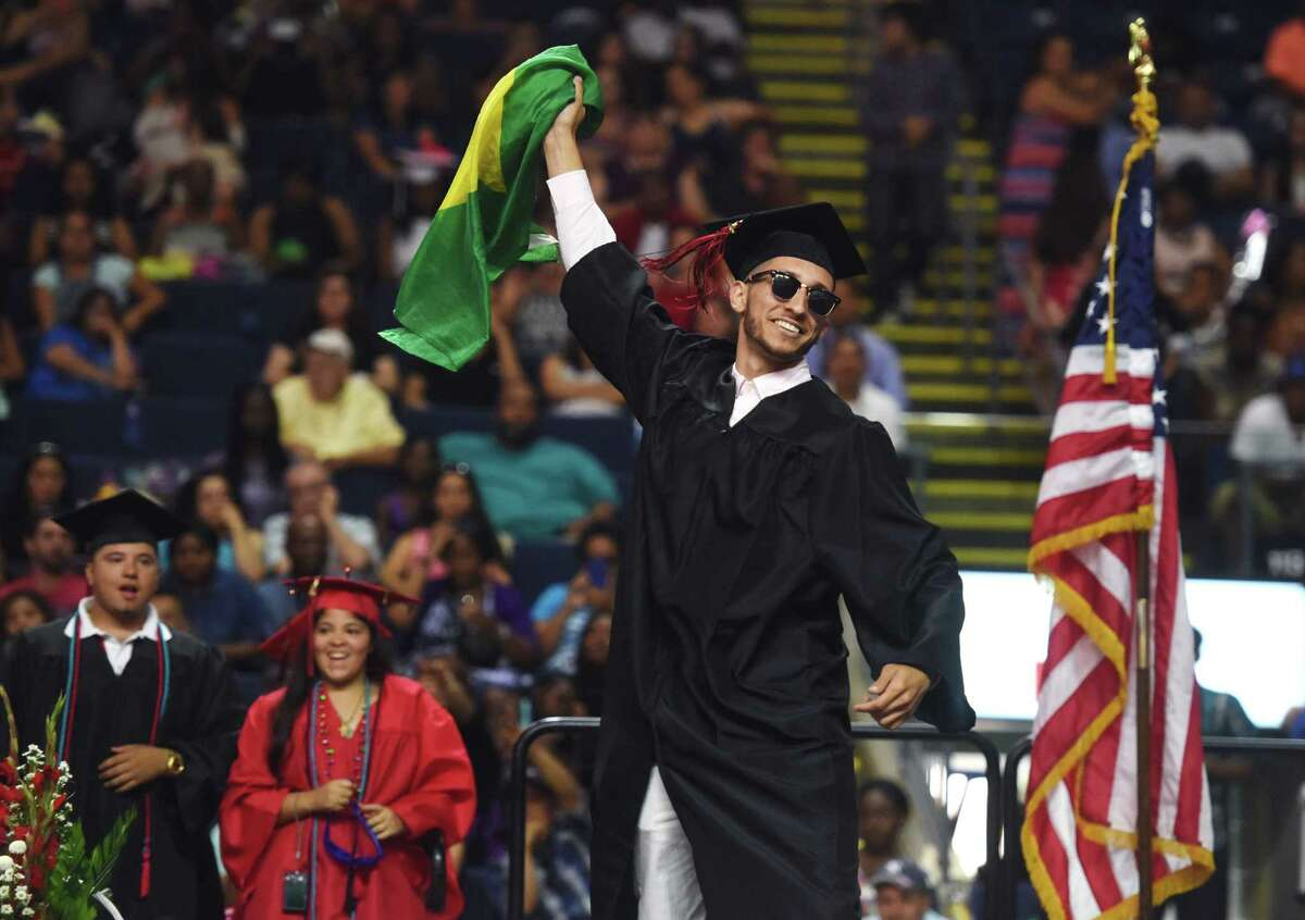 Pablo Rosa waves a Brazilian flag while walking across the stage to get his diploma during the Bridgeport Central High School 2015 graduation ceremony at Webster Bank Arena in Bridgeport, Conn. Monday, June 22, 2015.