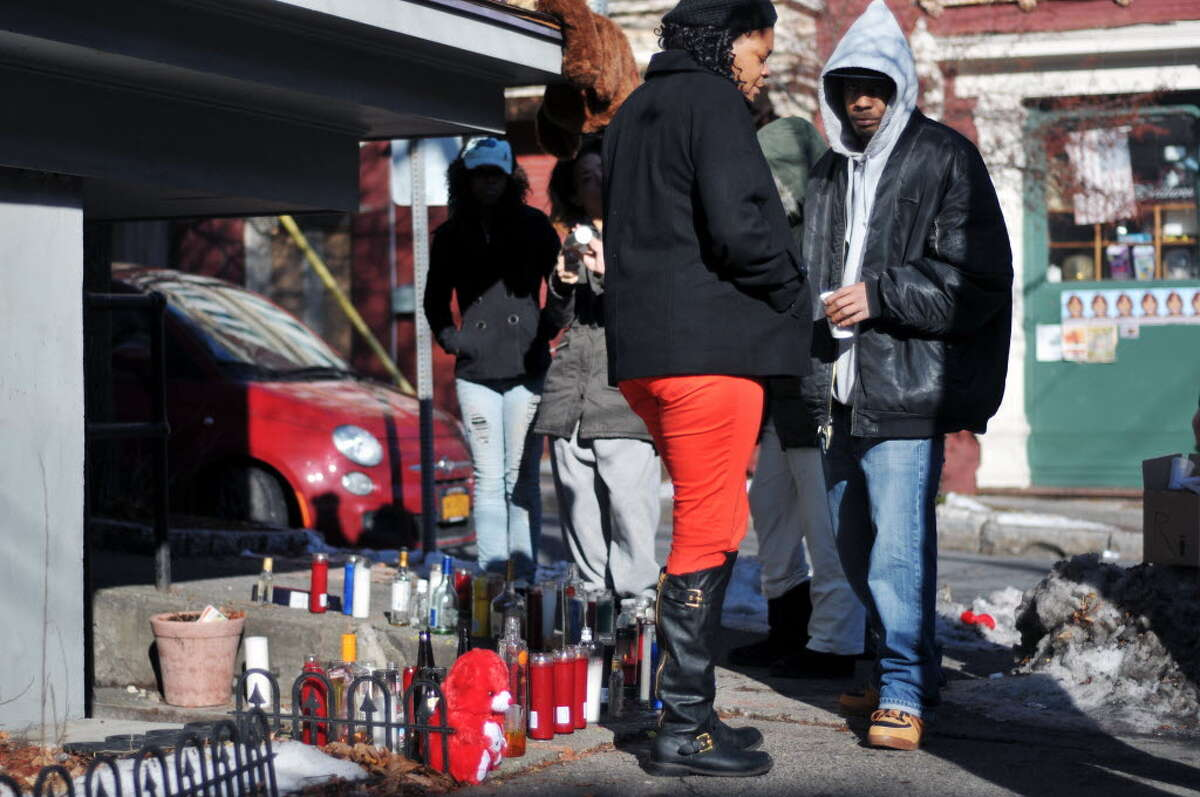 Nabresha Hicks, center, the wife of Sylvester Scott, visits a memorial set up on Grand St. in this photograph from Dec. 24, 2013. The memorial was set up near the site where Scott was fatally shot in Albany, NY. (Paul Buckowski / Times Union)