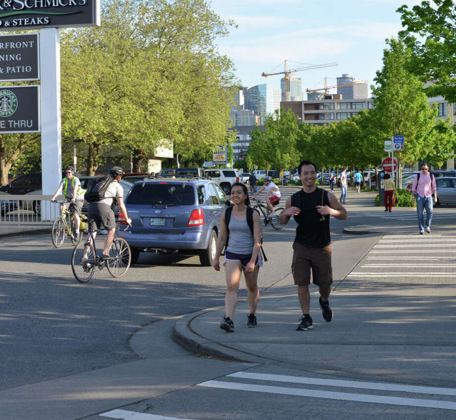 Cyclists pedal through the parking lot separating Westlake Avenue from businesses on Lake Union's western shore. A $3.6 million cycle track project would add 1.2 miles of protected, lighted bike path to that parking lot. It's meant to connect northwest Seattle with South Lake Union and downtown. Photo: City Of Seattle