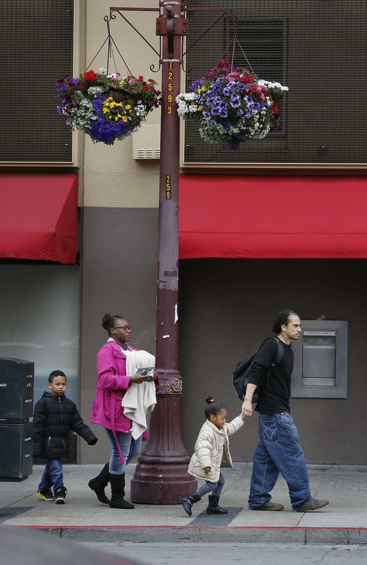 Ricardo Piedra (right) holds the hand of Jailyn Piedra (second from right) while Tamicka Crawford (second from left) carries Josiah Piedra (center), 1 month and is followed by Jeremiah Piedra (left), 6, all of San Francisco as they walk beneath flowers hanging from a lamp post on Mission Street between 21st and 22nd Streets on Monday, June 22, 2015 in San Francisco, Calif.