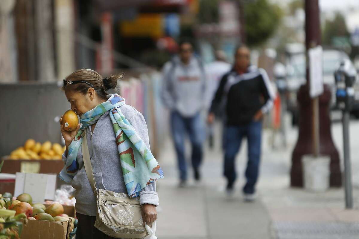 A shopper at Evergreen Market smells a piece of fruit while shopping on Mission Street between 21st and 22nd Streets on Monday, June 22, 2015 in San Francisco, Calif.