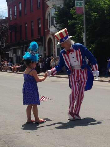 Scout Moutray, the daughter of Kimberly Moutray of Albany, meets Uncle Sam during the city of Troy's Flag Parade this month. (Kimberly Moutray)
