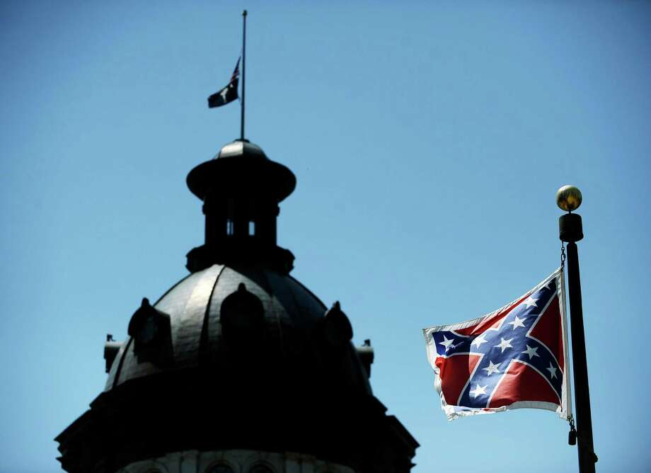 In this June 19, 2015, photo, a Confederate flag flies near the South Carolina Statehouse in Columbia, S.C.  Whether South Carolina should continue to fly the Confederate flag on its statehouse grounds is the latest in a series of issues to arise this summer challenging the GOP's effort to build the young and diverse coalition of voters it likely needs to win the White House.  (AP Photo/Rainier Ehrhardt) ORG XMIT: WX110 Photo: Rainier Ehrhardt / FR155191 AP