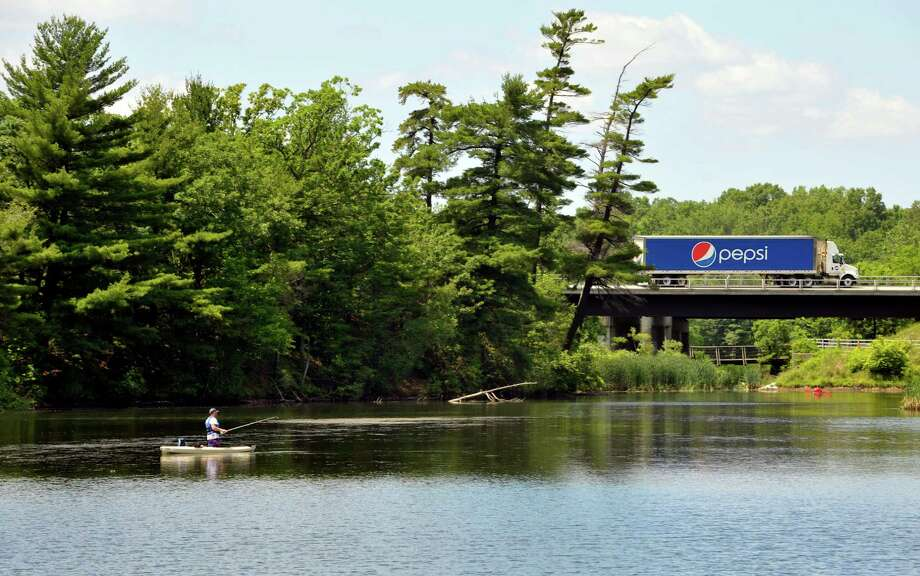 Traffic heads north on Interstate 87 as a man fishes from a kayak in Rensselaer Lake on Monday, June 22, 2015, in Albany, N.Y.    (Paul Buckowski / Times Union)