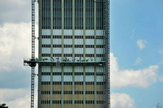Workers on scaffolding repair some windows and replace other windows on the Dutch Quad tower at the University at Albany on Monday, June 22, 2015, in Albany, N.Y. The work is part of the yearly refurbishing the college performs on the housing for students on a rotating basis.    (Paul Buckowski / Times Union)