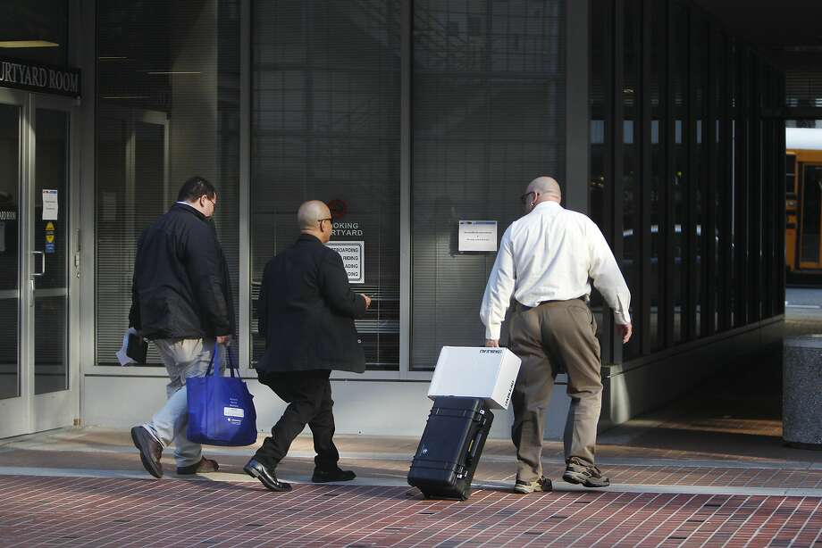 Agents with the state attorney general's office carry a bag and rolling case with a box as they leave the California Public Utilities Commission's San Francisco headquarters in November 2014. The agents had executed a search warrant in connection with a criminal probe into possible violations of influence-peddling or other laws in connection with back-channel talks with PG&E. Photo: Lea Suzuki, The Chronicle