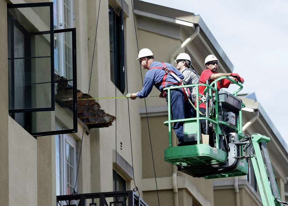 FILE- In this Wednesday, June 17, 2015 file photo, a worker measures near the remaining wood from an apartment building balcony that collapsed in Berkeley, Calif. The balcony broke loose from the building during a 21st birthday party early Tuesday, killing several people and seriously injuring others. The seven Irish students who survived the collapse remain hospitalized in varying states of recovery nearly a week later. (AP Photo/Jeff Chiu, File) ORG XMIT: FX304 Photo: Jeff Chiu / AP