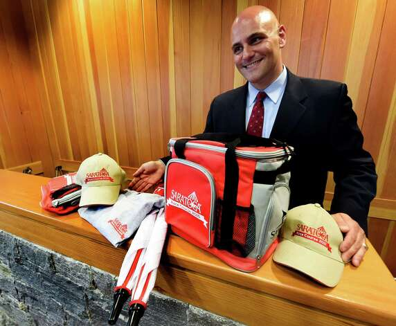 John Durso Jr., director of NYRA public relations shows off all the giveaways for the 2015 meeting of the Saratoga Race course which is a baseball cap, umbrella, t-shirt and a cooler bag which were previewed during a press briefing Monday June 22, 2015 at the Fasig Tipton pavilion in Saratoga Springs, N.Y.    (Skip Dickstein/Times Union) Photo: SKIP DICKSTEIN / 00032328A
