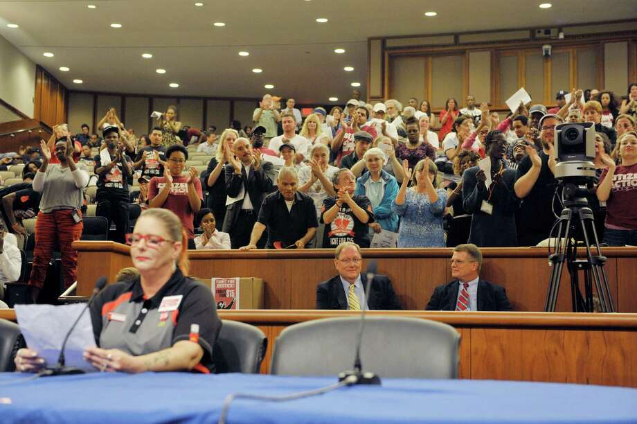 Albany McDonald's worker, Jaquie Jordan, gets a standing ovation from supporters of raising the minimum wage, as Jordan addressed the wage board during the final hearing of the board as it considers raising the minimum wage for fast-food workers on Monday, June 22, 2015, at the Legislative Office Building in Albany, N.Y. Jordan told the board that her husband can't work due to a disability and that with her job at McDonalds she can barely make ends meet. Jordan said that she must walk to work, a half-hour each way, because she can't afford bus fare.    (Paul Buckowski / Times Union) Photo: PAUL BUCKOWSKI / 00032359A