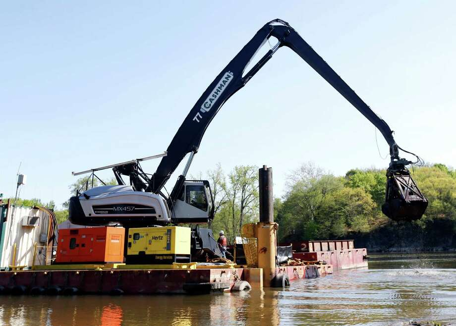 FILE - In this May 7, 2015 file photo, crews perform dredging work along the upper Hudson River in Waterford, N.Y. Long after the last dredging barge leaves the upper Hudson River, scientists will track the slow fade in contamination levels. General Electric Co. expects to finish this year removing some 2.7 million cubic yards of contaminated river sediment under its landmark Superfund agreement with the federal Environmental Protection Agency. After six years of digging, crews will have removed most of the PCBs on the river bottom discharged decades ago from two GE plants upriver. (AP Photo/Mike Groll, File) ORG XMIT: NYMG402 Photo: Mike Groll / AP