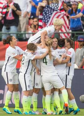 The United States's Megan Rapinoe jumps on top of her teammates as they celebrate Alex Morgan's goal during their FIFA Women's World Cup Group of 16 Match against Colombia at Commonwealth Stadium in Edmonton, Canada on June 22, 2015.   AFP PHOTO/GEOFF ROBINSGEOFF ROBINS/AFP/Getty Images
