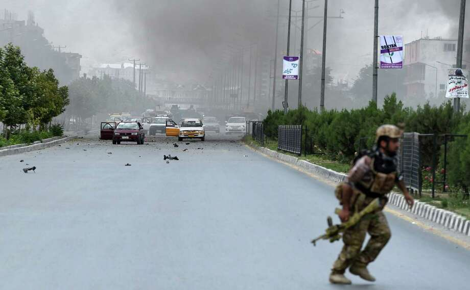 A security official runs at the site of an attack in front of the Parliament building in Kabul. Photo: Shah Marai /Getty Images / AFP