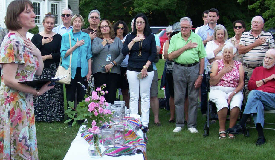 "Rev. Alison Patton, pastor of the Saugatuck Congregational Church, asked those attending Monday's vigil on the front lawn of the church to place their hand on their chest ""to mark this moment"" and to ""welcome the spirit of God."" Photo: Anne M. Amato / Anne M. Amato / westport news"