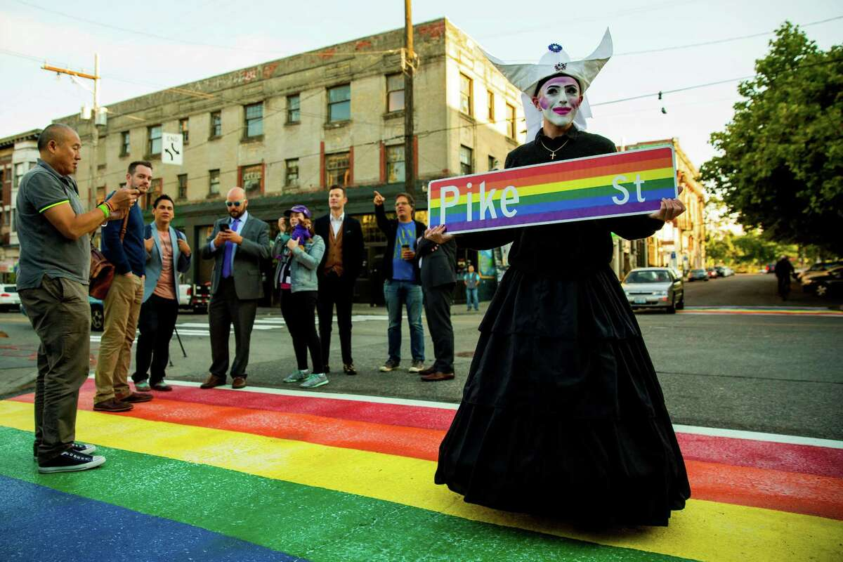 A member of The Sisters of the Mother House of Washington, right, poses for pictures on the newly-installed, rainbow-colored crosswalks in various locations around Capitol Hill, photographed Tuesday, June 23, 2015, at the intersection of 10th and Pike Street in Seattle, Washington.  (Jordan Stead, seattlepi.com)
