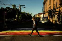 Passerby navigate the newly-installed, rainbow-colored crosswalks in various locations around Capitol Hill, photographed Tuesday, June 23, 2015, at the intersection of 10th and Pike Street in Seattle, Washington.