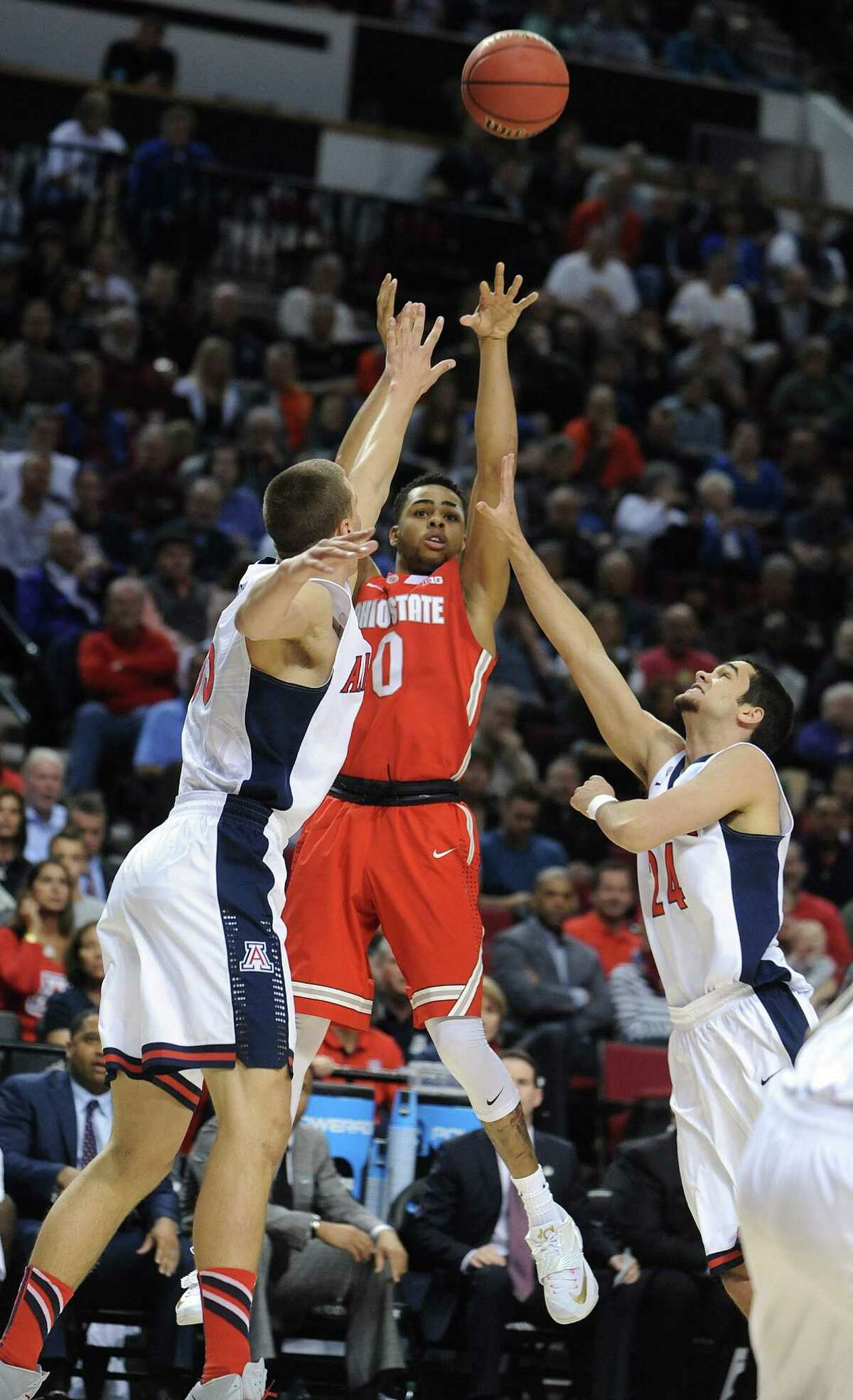 Ohio State guard D'Angelo Russell shoots between Arizona guard Elliott Pitts, right, and Arizona center Kaleb Tarczewski during an NCAA tournament round of 32 game in Portland, Ore.