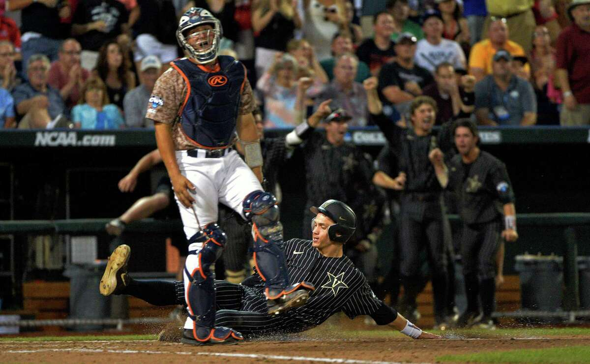 Vanderbilt's Bryan Reynolds scores on a two-run double by Will Toffey as Virginia catcher Matt Thaiss looks on during the sixth inning of Game 1 of the best-of-three NCAA baseball College World Series finals at TD Ameritrade Park in Omaha, Neb., Monday, June 22, 2015.