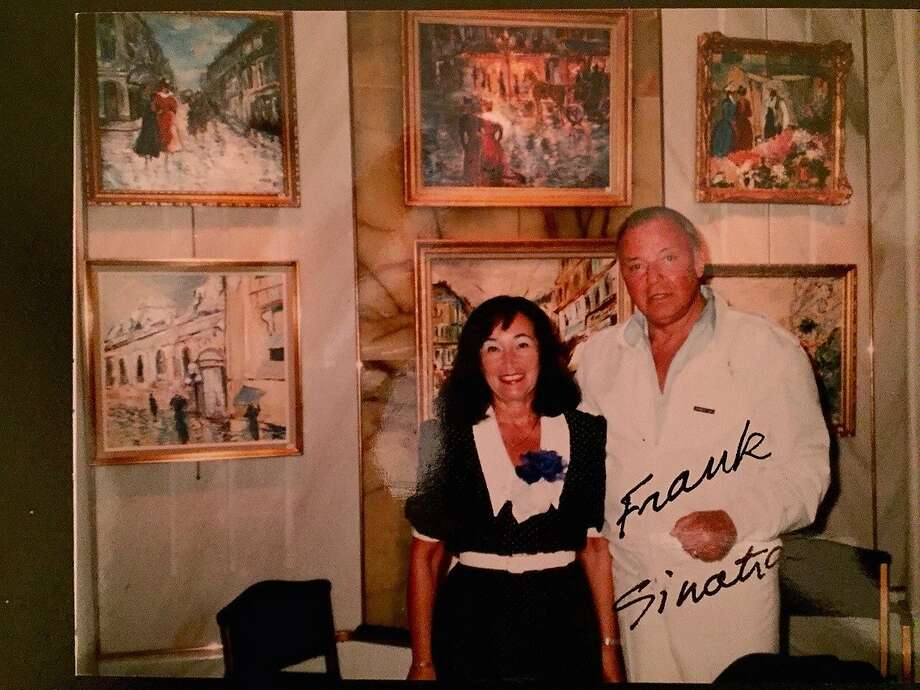 Nadine Sacha pictured with Frank Sinatra (Right) — her artwork behind them — at one of her art showcases at the Hotel de Paris in Monte Carlo in 1986. Frank and Barbara Sinatra purchased many of Nadine's paintings in the past.  *Photo courtesy of Nadine Sacha. Photo: Photo Courtesy Of Nadine Sacha.