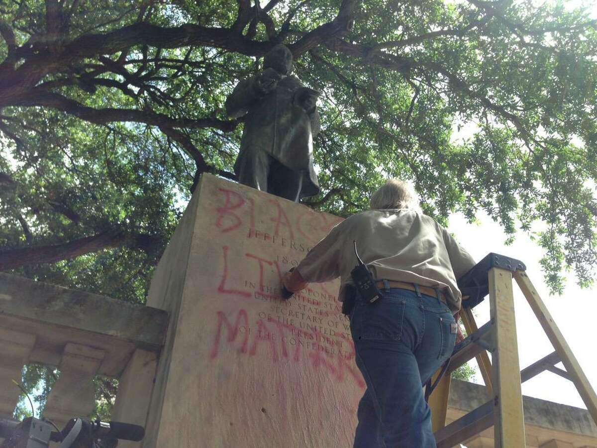 Workers clean paint off of a Jefferson Davis statue on UT Austin campus.