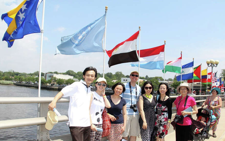Visitors to Westport for a recent jUNe Day stand amid a panoply of nations' flags on the Ruth Steinkraus Cohen Bridge, named for the founder of the annual exchange program. Photo: Carroll Hubbard / Contributed Photo / Westport News