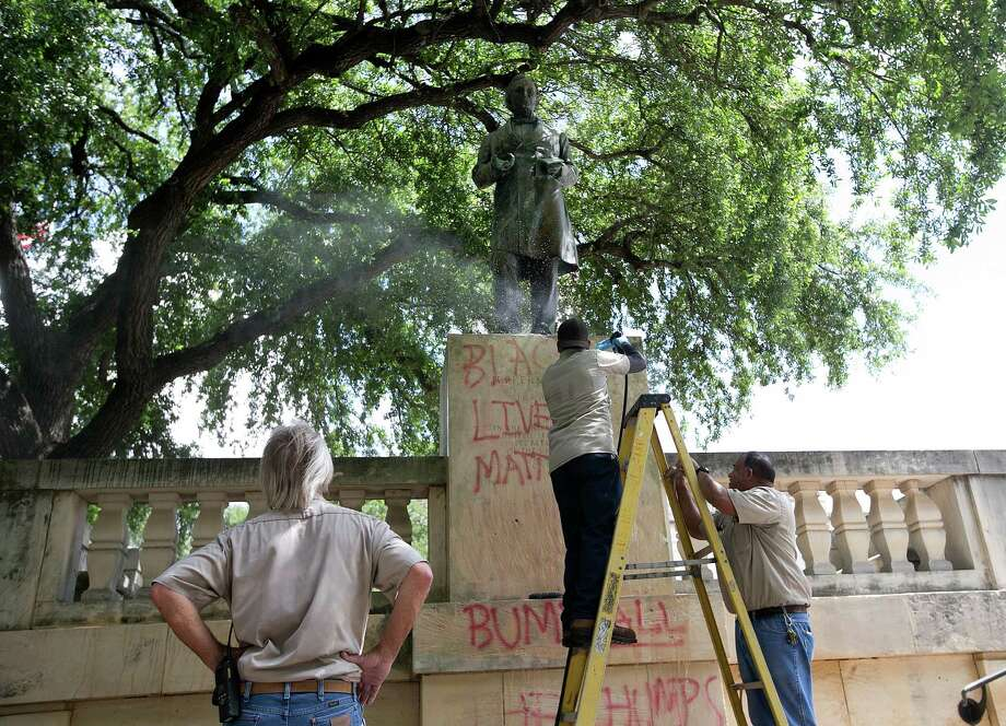 """Sergio Martinez, center, with UT Facilities Services, pressure washes a statue of Jefferson Davis to remove graffiti at the University of Texas campus in Austin, Texas, on Tuesday, June 23, 2015.  Cindy Posey, spokeswoman for campus security at UT, says """"Black lives matter"""" was scrawled early Tuesday on the base of the statue to the president of the Confederacy, and also on those for Confederate Gens. Robert E. Lee and Albert Johnston.   (Dborah Cannon/Austin American-Statesman via AP) Photo: Dborah Cannon, Associated Press / Austin American-Statesman"""