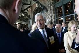 "Jamie Dimon, chairman and chief executive officer of JPMorgan Chase & Co., center, talks with attendees before speaking at the Chicago Executives Club in Chicago, Illinois, U.S., on Wednesday, June 10, 2015. Dimon took aim at U.S. Senator Elizabeth Warren, a critic of large banks, as he expressed broad concerns about leadership in Washington saying ""I don't know if she fully understands the global banking system."" Photographer: Tim Boyle/Bloomberg *** Local Caption *** Jamie Dimon"