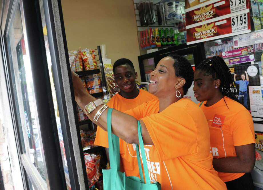New Neighborhoods employee Vonda Pommills and her children, Derrick and Christian, 14, put up a poster at Two Brothers Supermarket to raise awareness of the CT No Kid Hungry Campaign in Stamford on Tuesday. Photo: Tyler Sizemore / Hearst Connecticut Media / Greenwich Time