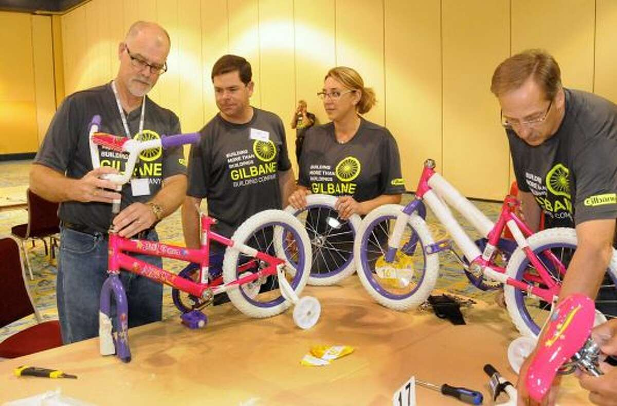 Gilbane Building Company President and COO Mike McKelvy, left, Senior Vice President Dan Gilbane, Vice President Lisa Martin and Director of Finance Paul D'Ambrosio build bicycles for children during the company's annual leadership meeting June 9. The company constructed 75 bikes that were donated to Montgomery County charities.
