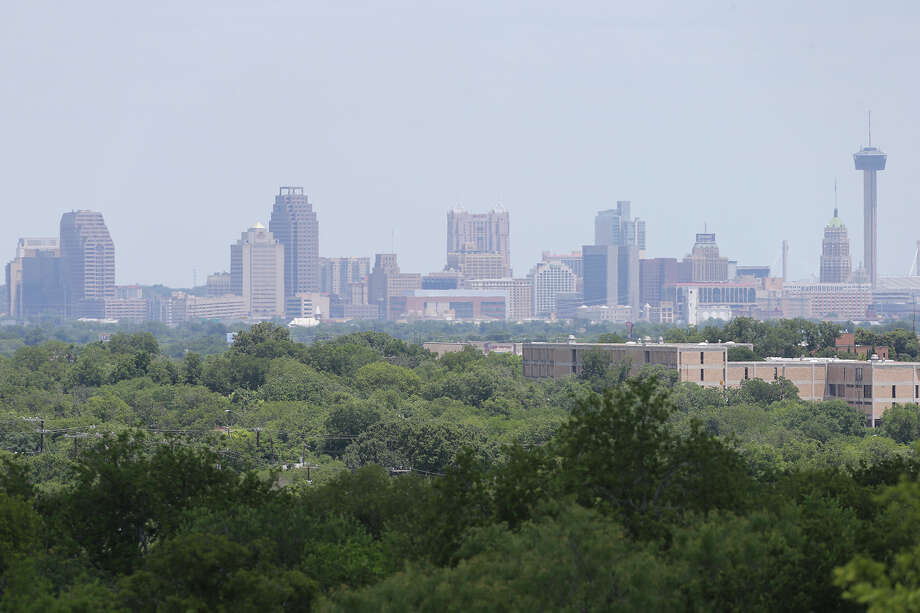 Haze lingers over the downtown skyline mid day on July 11, 2013. Figures from local monitoring stations show a reduction since 2013 in ground-level ozone. But local officials are worried that pollution from oil and gas production and a possible adoption of more stringent federal standards could knock San Antonio out of compliance for air quality. Photo: TOM REEL /San Antonio Express-News / San Antonio Express-News