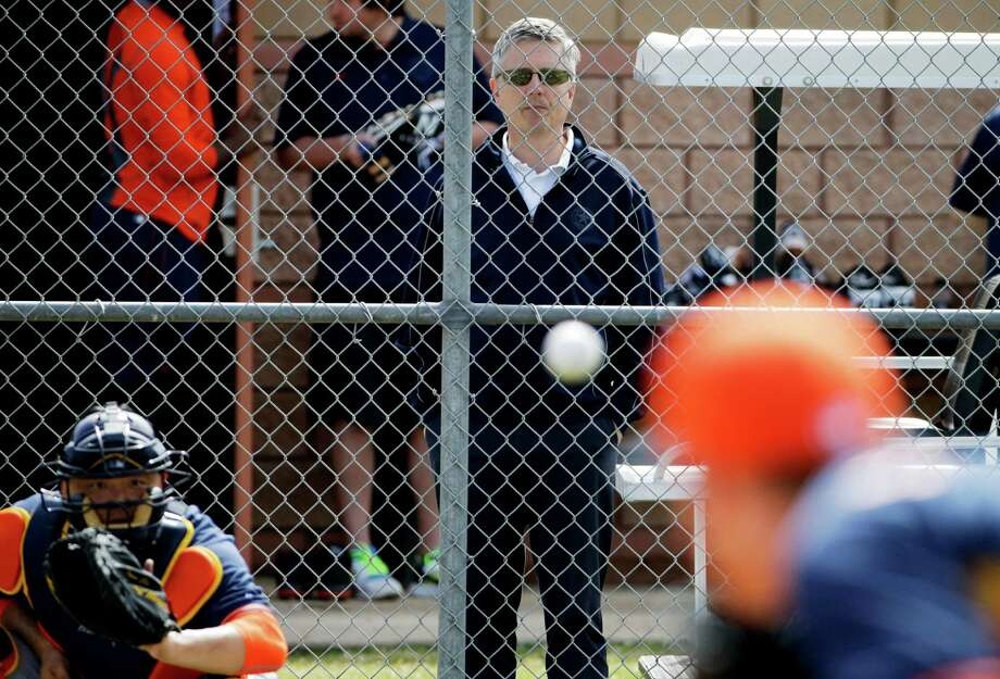 Houston Astros general manager Jeff Luhnow, center, watches pitcher Dan Straily, right, throw to catcher Hank Conger, left, during a spring training baseball workout in Kissimmee, Fla., on Feb. 21, 2015. Federal law enforcement authorities are investigating whether the St. Louis Cardinals illegally accessed a computer database of th Astros. The aim was obtaining information from the front office headed by Luhnow, a former top aide who helped transform St. Louis' scouting operation to a sabermetrics-based system, a person familiar with the situation told the Associated Press. Photo: David Goldman /Associated Press / AP