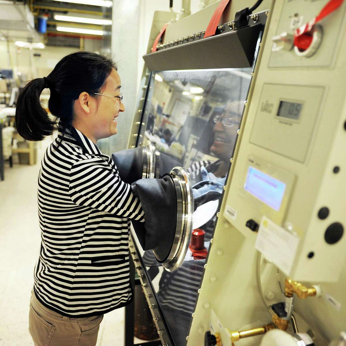 Research scientist Shasha Zhang works in the Glove Box, a controlled environment used for manufacturing BESS Tech's batteries in a SUNY Poly campus lab at CNSE Tuesday June 23, 2015 in Albany, NY. (John Carl D'Annibale / Times Union)