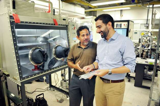 SUNY Poly VP Pradeep Haldar, left, and BESS Tech's Fernando Gomez-Baquero discuss battery technology in a SUNY Poly campus lab at CNSE Tuesday June 23, 2015 in Albany, NY.  (John Carl D'Annibale / Times Union) Photo: John Carl D'Annibale / 00032365A