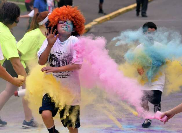 Justin Montrose gets blasted with color during the Color-a-thon, running race as part of the final days of school Tuesday morning, June 23, 2015, at School 16 in Troy, N.Y.  The event was  fundraiser for the PTA.   (Skip Dickstein/Times Union) Photo: SKIP DICKSTEIN / 00032326A